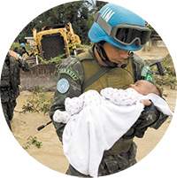 Port au Prince, Haiti - Brazilian UN peacekeeper rescues a child from his flooded home in Cite Soleil. Haevy rains from tropical storm Noel left thousends homeless.